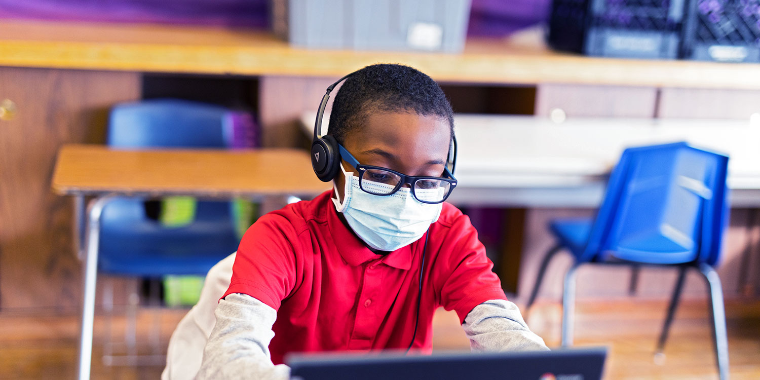 Masked student wearing headphones and looking at laptop at their desk.