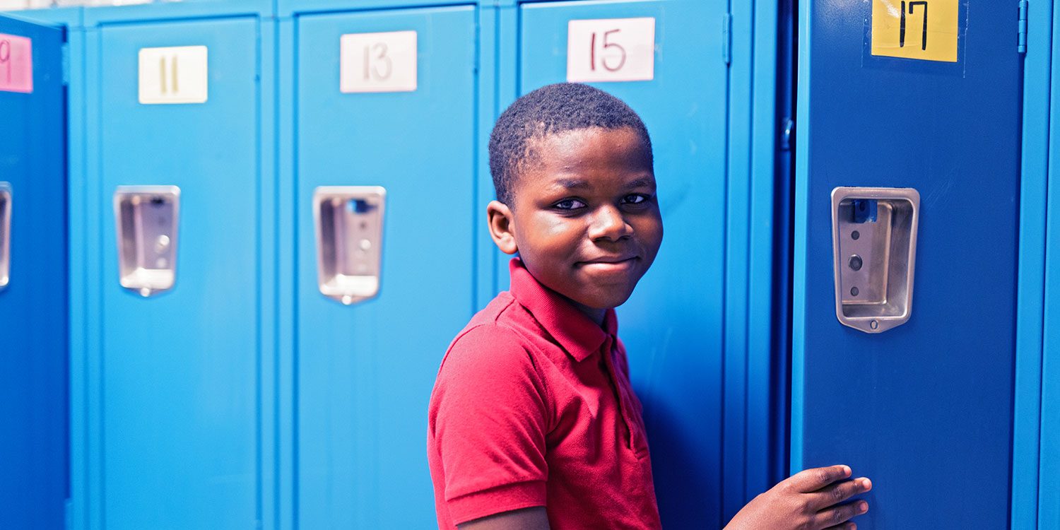Smiling student standing in hallway at their locker.