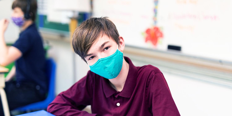 Masked student at desk.