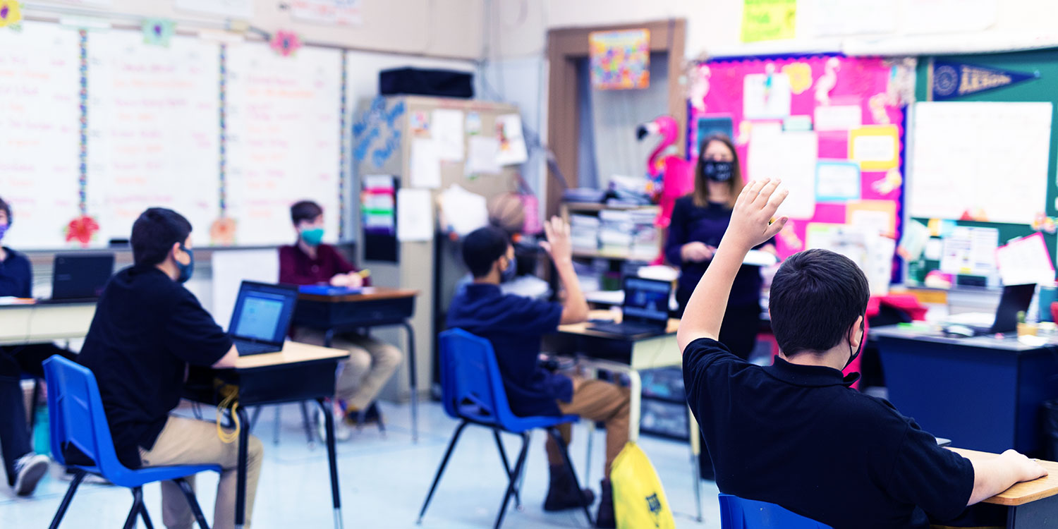 Students sitting at desks with their hands raised in a classroom.