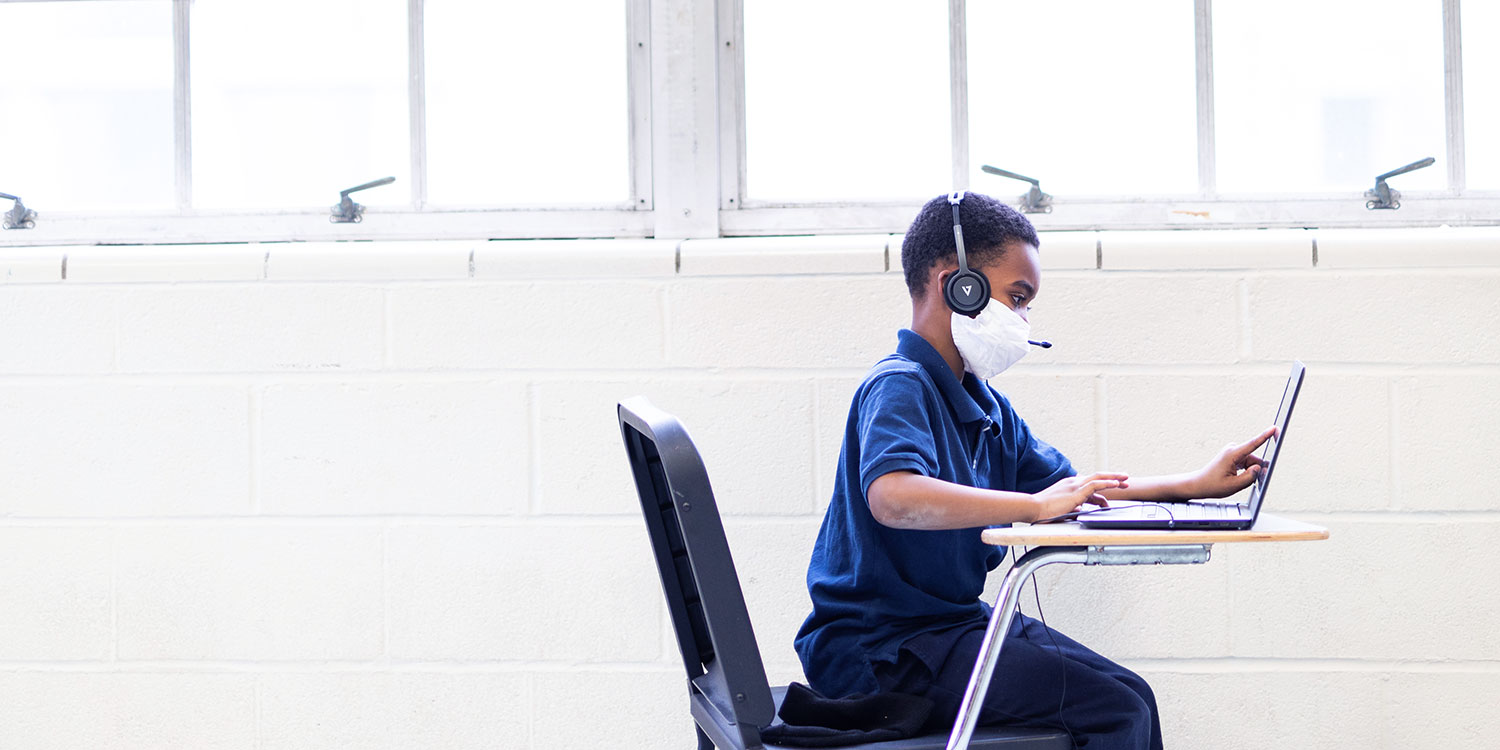 Student at desk with laptop and headphones.