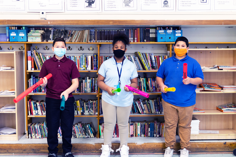 Three students standing and holding rhythm sticks.