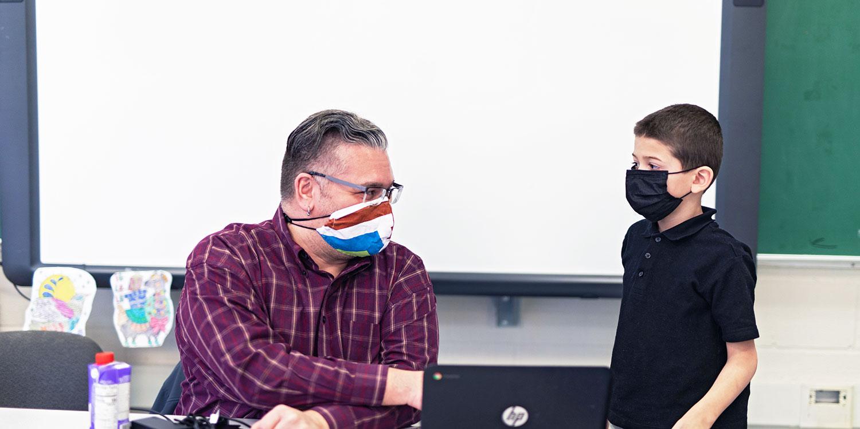 Teacher talking to student at desk.