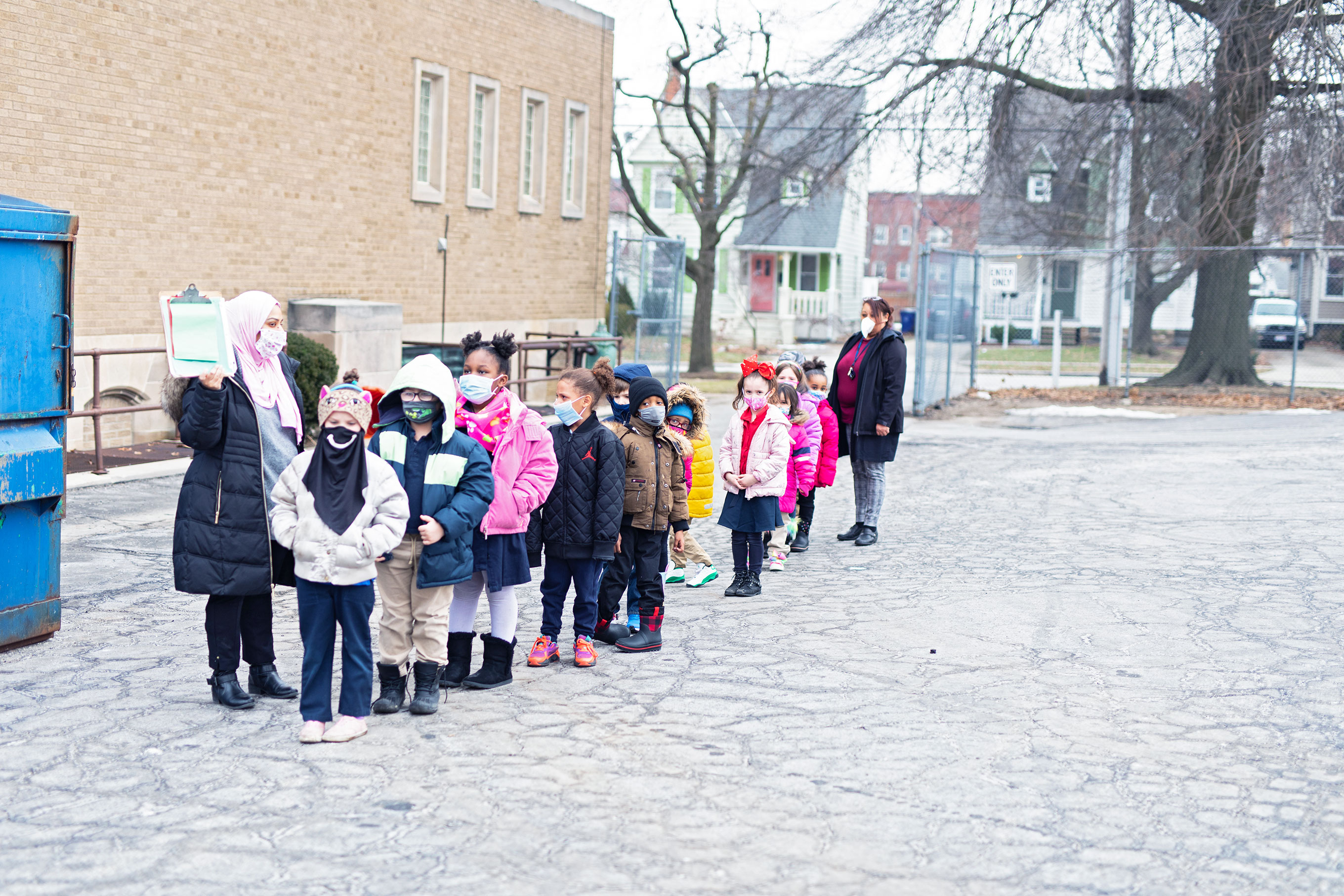 Elementary students forming a line outside the school.